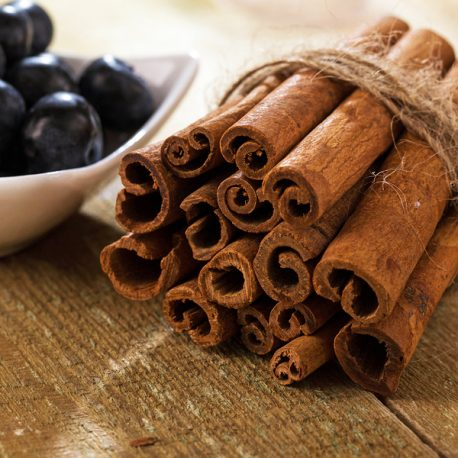 Stack of cinnamon wrapped with a rope and a plate with blueberries over a wooden surface